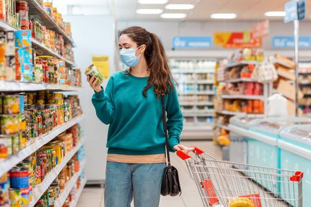 Shopping. A young pretty Caucasian woman in a medical mask buys a can of canned peas at a grocery store. The concept of buying products and the coronovirus pandemic.