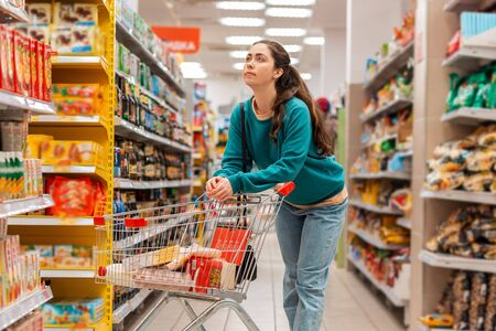 A young beautiful Caucasian woman leaning on a grocery cart, selects products in the store. Shelves with a variety of products in the background. The concept of shopping and buying products.