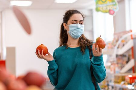 Shopping. Portrait of a young Caucasian woman with a medical mask on her face, holding a pear and a pomegranate, choosing between them. The concept of buying fruit and protecting against coronovirus.