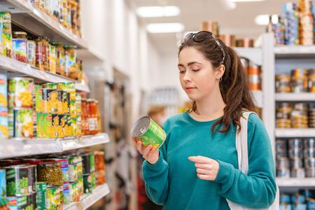 Eine junge hübsche kaukasische Frau liest Zutaten auf einer Dose Erbsenkonserven. Das Konzept des Kaufs von Produkten und des Einkaufens.