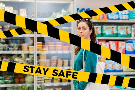 Do not cross.Barrier tape-quarantine,isolation.A young pretty Caucasian woman with an eco-bag on her shoulder, posing against the background of refrigerators with food. The concept of coronavirus and quarantine.