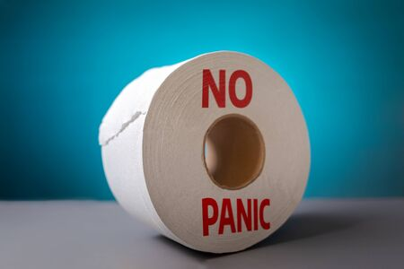 A roll of toilet paper on blue background close-up. The concept of panic purchasing of essential goods. Coronovirus, pandemic, hygiene. No panic.