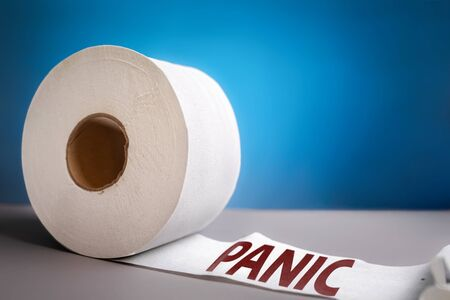 A roll of toilet paper on blue background close-up. The concept of panic purchasing of essential goods. The inscription panic on paper. Coronovirus, pandemic, hygiene.