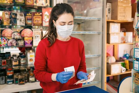 A woman in rubber gloves and a medical mask counts the money from the sale. In the background are shelves of the store. The concept of coronovirus and the crisis in business.