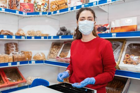 A portrait of woman in rubber gloves and a medical mask puts money in the cash register. In the background are shelves of the store. The concept of coronovirus and the crisis in business.