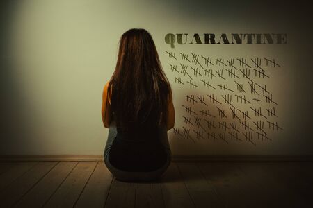 A young woman is sitting on the floor in a dark room, facing the wall on which the days of the calendar are crossed out. Rear view. Concept of coronavirus, self-isolation and pandemic.