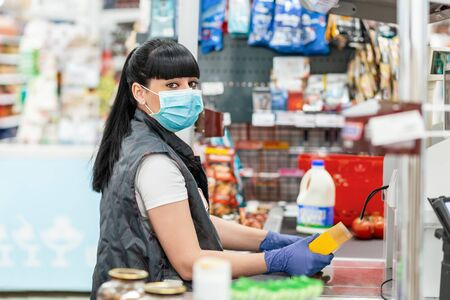 A young woman in a medical mask and gloves, working at the checkout in a supermarket. Concept of coronavirus, protection from infection and industrial crisis.