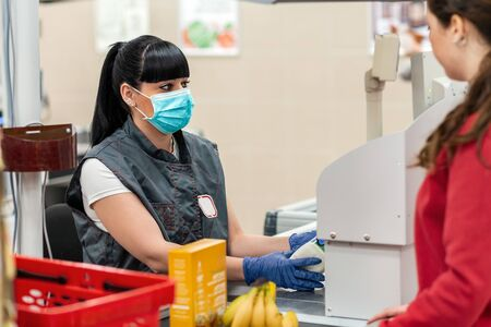 A young woman in a medical mask and gloves, working at the checkout in a supermarket. In the foreground is a customer in a blur. Close up. Concept of coronovirus, protection from infection and industrial crisis. Foto de archivo