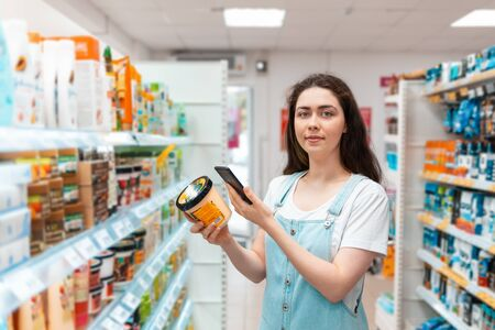 Shopping. A beautiful young woman scans the composition of the body cream. Modern technology in everyday life.