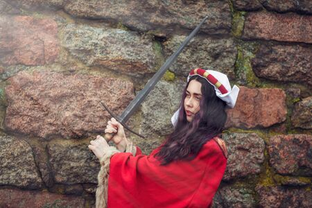 the girl swung the sword near the stone wall. Stock fotó
