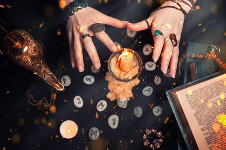 Astrology and esotericism. Female witch hands conjure over a candle. On a black background lie fortune-telling runes, a book, precious amulets, a copper lamp and a candle. Sparks of fire in the air.