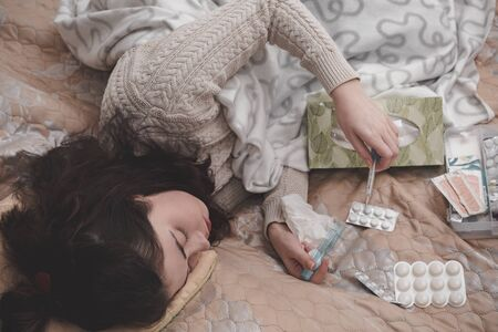 a sick girl in a sweater lying on the bed checks the temperature with a thermometer on the background of pills scattered on the blanket.