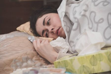 sick with the flu, a young girl lies in bed and holds the medicine in her hands.