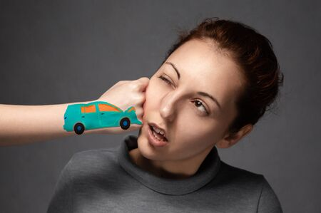 the concept of car accidents, insurance claims . close-up of the accident.The girl is hit by a turquoise car .a punch in the face of a young girl .Fist in the form of drawn machines