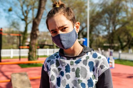 Portrait of a teenage boy in a medical mask, standing on the street in the Park, horizontal bars in the background. Sunny day. Concept of coronavirus, Allergy and protection from bacteria.