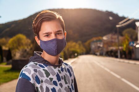 A teenage boy with a medical homemade mask on his face, posing against the background of an empty road and street. Copy space. Concept of quarantine, coronavirus and protection from bacteria.