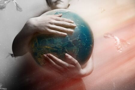 Woman embracing the globe of planet Earth. The concept of preserving the environment and love for your planet. Red and white drammatic tint. Light.