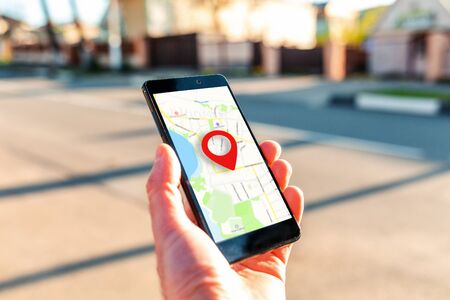 Male hand holding holding smartphone with online-a map on which the geolocation icon. In the background, a blurred street. Close up. Concept of online navigation and GPS. Banque d'images