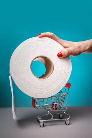 A woman's hand with a red manicure puts a roll of toilet paper on a small cart. Turquoise background. Close up. Concept of coronovirus, panic shopping and hygiene.