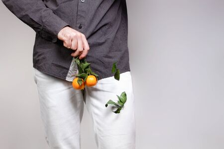 Concept of male sexual diseases. A man at the level of the genitals holds tangerines or oranges on a twig, from which the leaves fall off. Testicular cancer. Stock Photo