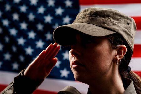 Memorial day. A portrait of female soldier in uniform salutes against the background of the American flag. Side view. The concept of the American national holidays and patriotism.