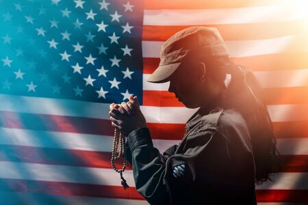 Memorial day, veterans day. A young woman holds a rosary in her hands and prays. American flag on the background. Copy space. Concept of American holidays and religion.