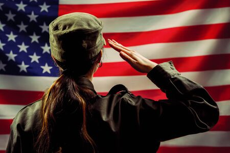 Veterans Day, Memorial Day, Independence Day. A female soldier salutes against the background of the American flag. Rear view. The concept of the American national holidays and patriotism.