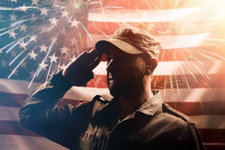 Memorial day. A soldier in uniform salutes against the background of the American flag with fireworks. The concept of the American national holidays and patriotism. Stock Photo
