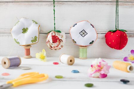 Handmade toys hanging on the wall. Biscornus and pin cushion. White desk background. Decoration and style.