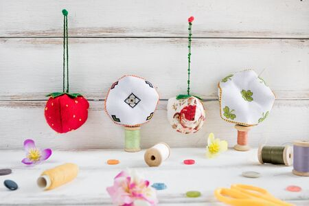 Handmade and needlework. Pin cushion with a simple ornament and a pair of scissors on a white table. Sewing supplies in the background. Copy space. 写真素材