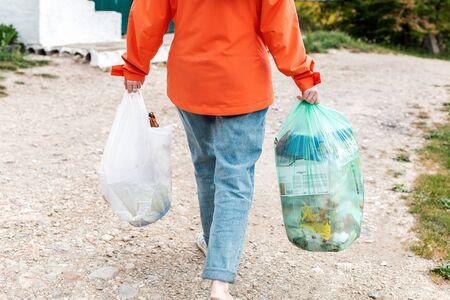 Garbage. The woman goes with two bags of garbage to throw them into the container. Outdoor. Rear view and close up. Concept of pollution environmental pollution and zero waste.