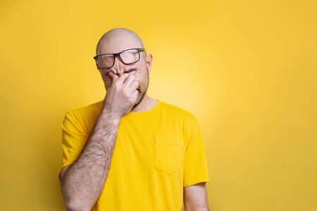 A bald man lifts his glasses on his forehead and rubs his eyes from fatigue or pain. Yellow background. opy space. Concept of health and psychology.