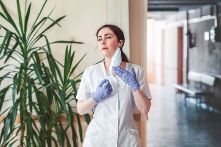 Coronavirus. Doctor in a medical gown and gloves, resting in the corridor of the hospital, removing the mask. The concept of hero doctors and the stress of overloading at work during a pandemic.
