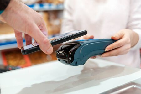 A woman's hands are held by a payment terminal and a man pays for a purchase using a smartphone. Side view. The concept of NFC, business and banking transactions.