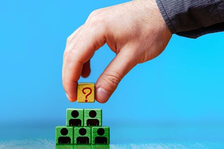 Human resource management and recruitment business concept. Hand putting wood cube block on top pyramid with sign of question. Copy space. Blue background. Stock Photo