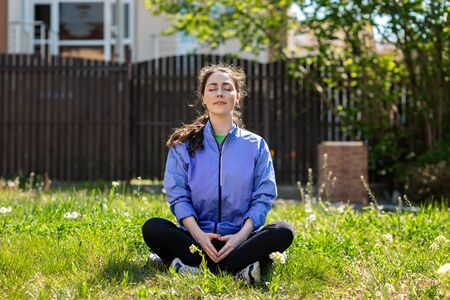 Spring and sports. A young pretty woman meditates cross-legged on the lawn of her yard. Concept of sports activity and yoga.