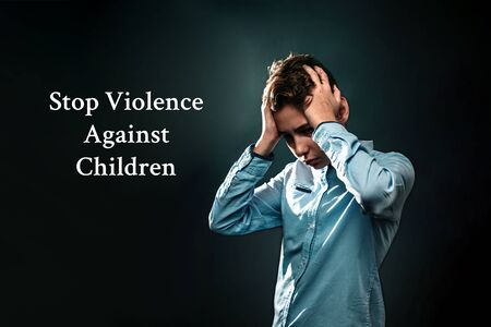 The concept of domestic violence. A teenage boy holds his hands over his head, experiencing stress. Text Stop violence against children . Black background.