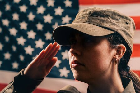 Memorial day. A close up portrait of female soldier in uniform salutes against the background of the American flag. The concept of the American national holidays and patriotism.