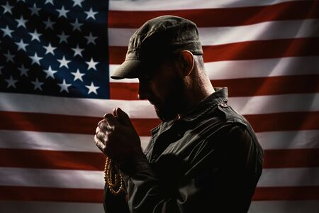 Memorial day, veterans day. Portrait of a Soldier holding a rosary and praying. American flag on the background. Dark colors. Concept of American holidays and religion