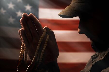 Memorial day, veterans day. A soldier holds a rosary in his hands and prays holding it to his face. Close up. American flag on the background. Concept of American holidays and religion.