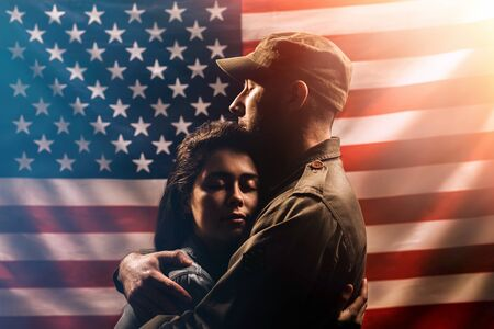 Veterans Day, Memorial Day. A soldier embraces his woman. Couple on the background of the American flag. The concept of the American national holidays and patriotism