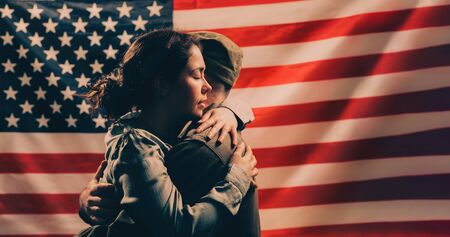 Independence day, memorial Day. A woman embraces a soldier. Couple on the background of the American flag. Copy space. The concept of American national holidays and patriotism. 写真素材