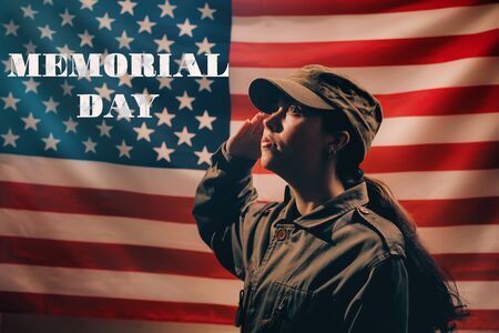 Memorial day. A female soldier in uniform salutes against the background of the American flag with the inscription Memorial day. Side view. The concept of the American national holidays and patriotism.
