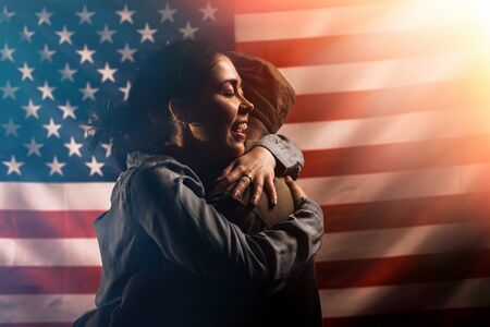 Independence day, memorial Day. The woman happily embraces the soldier. Couple on the background of the American flag. Copy space. Concept of American national holidays and patriotism
