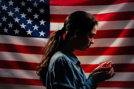 Memorial day. A woman holds a candle in memory of the victims. In the background, the American flag. Side view. Concept of American holidays.
