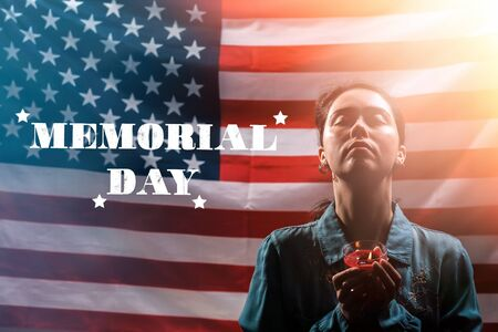 Memorial day inscription. A woman holds a candle in memory of the victims and raised her head with her eyes closed. The American flag is in the background. Concept of American holidays.