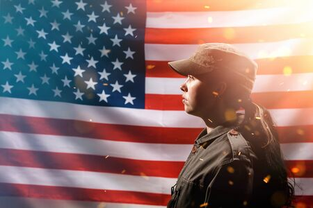 Memorial Day,Independence Day. Portrait of A female soldier in uniform, against the background of the American flag.Copy space. Side view. The concept of the American national holidays and patriotism.