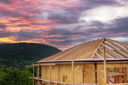frame eco-friendly house on the background of mountains and forests at sunset.