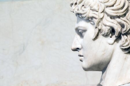 head of the statue close-up on white marble background with copy space.