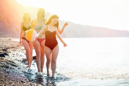 A group of beautiful young women in swimsuits cheerfully and carelessly walk along the water along the seashore. In the background, the sea and sky. Copy space. Concept of vacation, holiday at the sea.